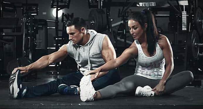 Urheilullinen mies ja nainen tekevät venyttelyä